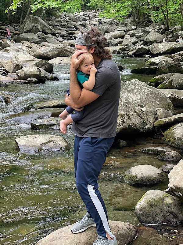 father and child playing in stream